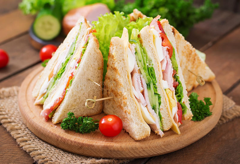 Club sandwich. With cheese, cucumber, tomato, ham and eggs stock photos