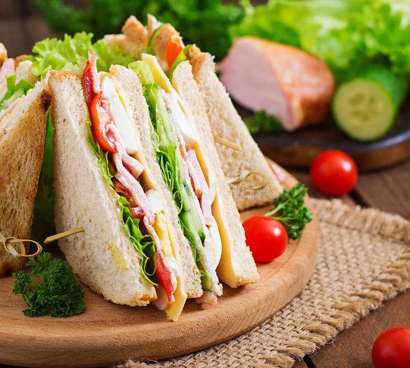 Club sandwich. With cheese, cucumber, tomato, ham and eggs royalty free stock images