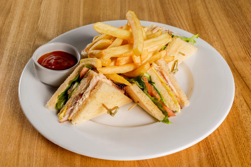 Club Sandwich with French Fries. Club Sandwich with Cheese, PIckled Cucmber, Tomato and Smoked Meat. Garnished with French Fries royalty free stock photography