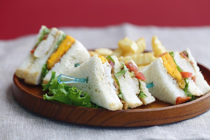 Club sandwich with fries. On a wooden plate royalty free stock image