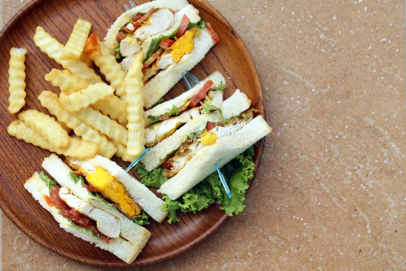 Club sandwich with fries. On a wooden plate stock image