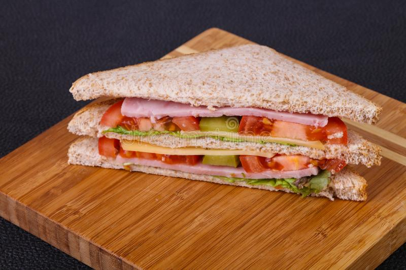 Club sandwich with ham and cheese. Club sandwich with ham , cheese, salad leaves, tomatoes and pickled cucumbers stock photos