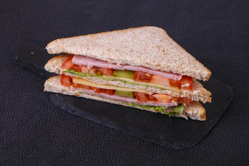 Club sandwich with ham and cheese. Club sandwich with ham , cheese, salad leaves, tomatoes and pickled cucumbers royalty free stock image
