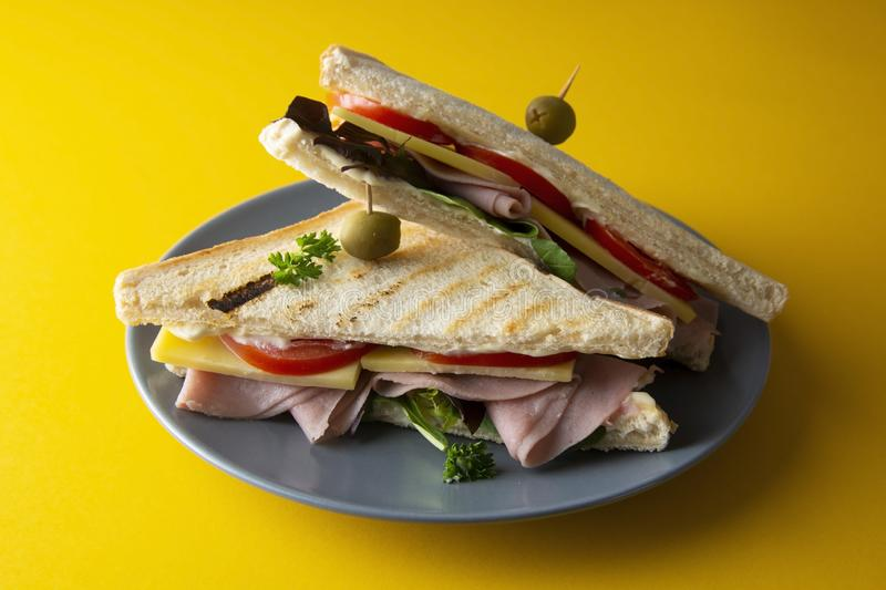 Club sandwich with ham isolated. Toasted double panini with ham, cheese fresh vegetables. Yellow background. Club sandwich with ham isolated. Toasted double royalty free stock photography