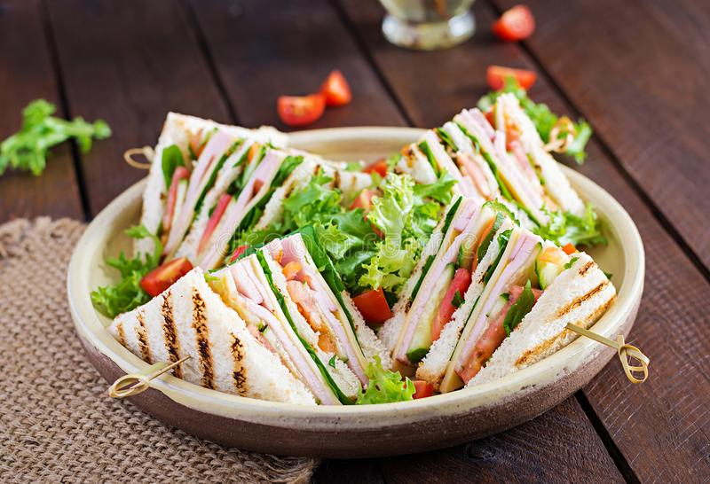 Club sandwich with ham, tomato, cucumber, cheese, and arugula royalty free stock photography
