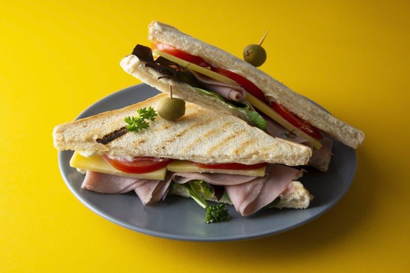 Club Sandwich mit dem Schinken lokalisiert Geröstetes doppeltes panini mit Schinken, Frischgemüse des Käses Gelber Hintergrund lizenzfreie stockfotografie