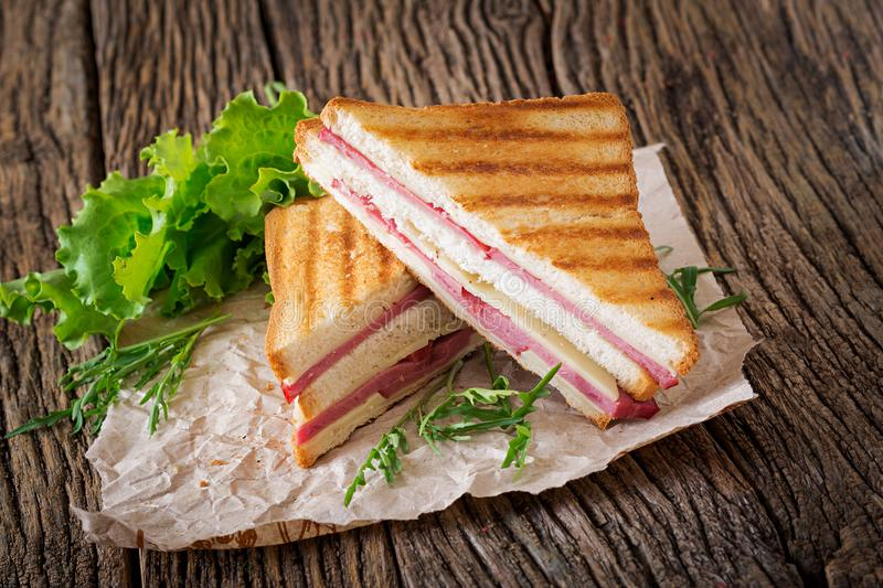 Club sandwich - panini with ham and cheese. On wooden background. Picnic food stock photography