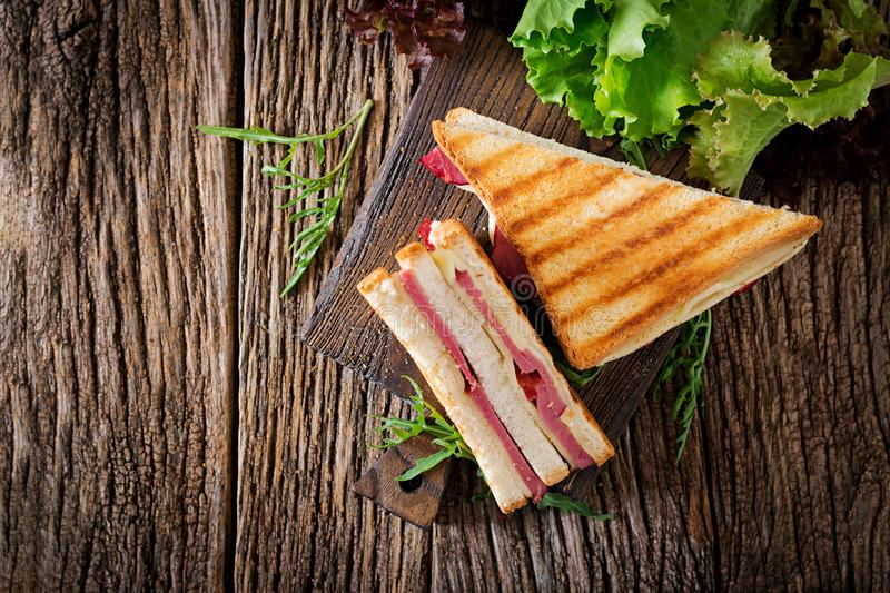 Club sandwich - panini with ham and cheese. On wooden background. Picnic food. Top view. Flat lay royalty free stock images