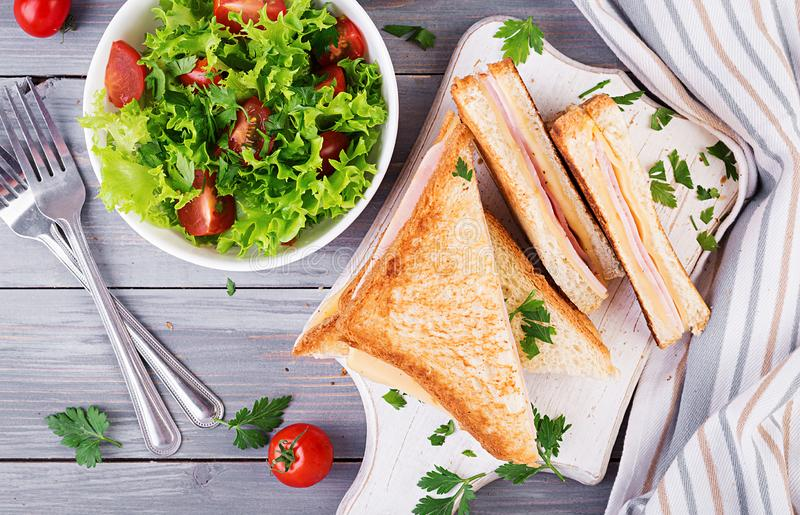 Club sandwich panini with ham, cheese and salad. Top view. stock photos