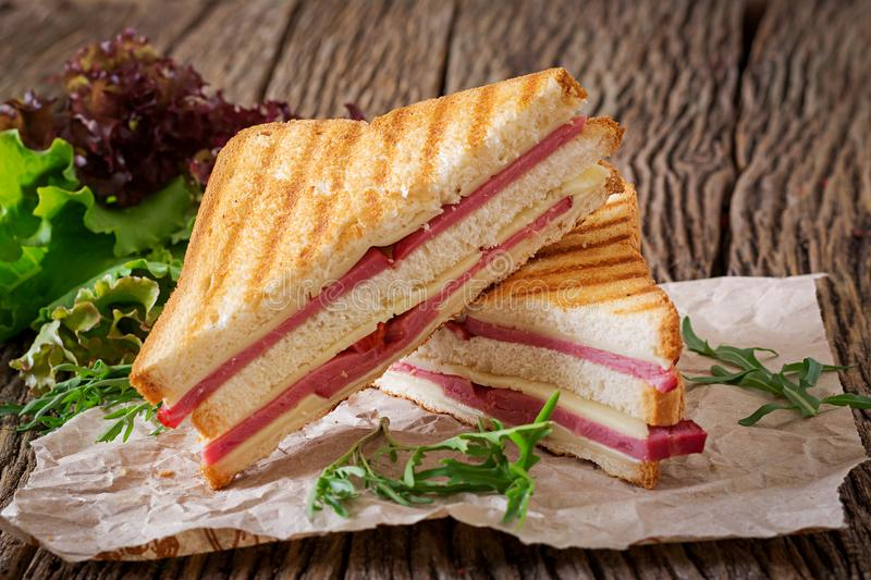 Club sandwich - panini with ham and cheese. On wooden background. Picnic food stock images