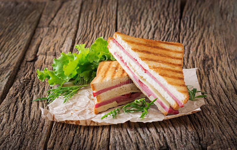 Club sandwich - panini with ham and cheese. On wooden background. Picnic food royalty free stock photo