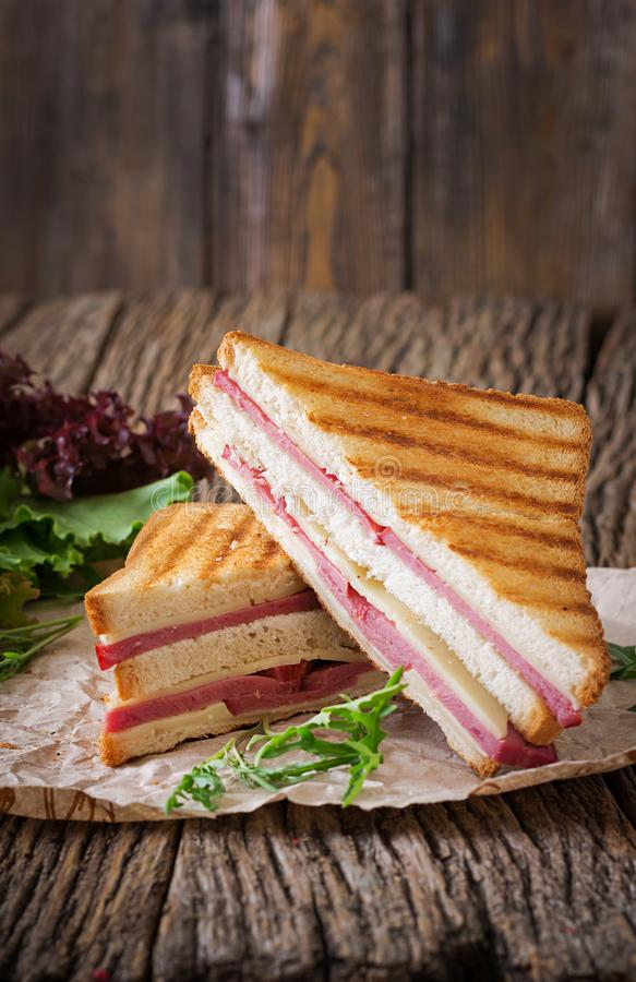 Club sandwich - panini with ham and cheese. On wooden background. Picnic food stock image