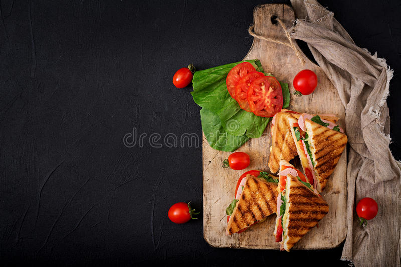 Club sandwich panini with ham. Tomato, cheese and basil. Flat lay. Top view royalty free stock images