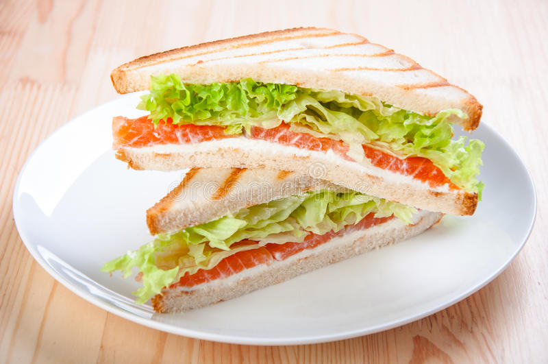 Club sandwich with salmon, cheese, lettuce royalty free stock photography