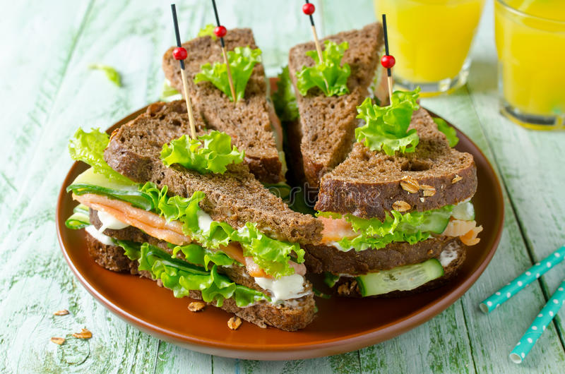 Club sandwich with salmon and cucumbers. On dark rye bread royalty free stock photo