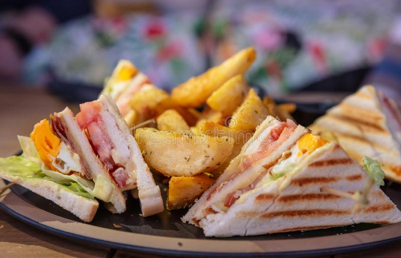 Club sandwich, take away food. Toasted bread slices, cheese, ham, egg, lettuce, french fries, closeup royalty free stock photo