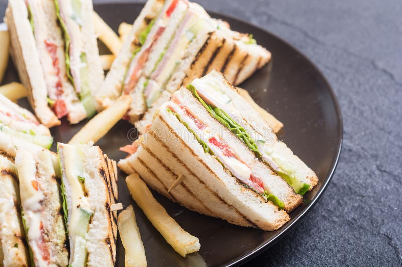 Club sandwich with tomatoes , cucumber , ham and cheese. Club sandwich with tomatoes , cucumber , ham , cheese and salad . Clubsandwich royalty free stock photography