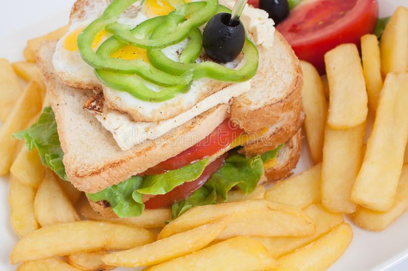 Club sandwich on a white plate with french fries and vegetables. Close up stock images