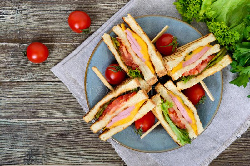 Club-sandwiches with crispy toast, sausage, cheese, tomato, greens. Traditional American snack. The top view royalty free stock photo