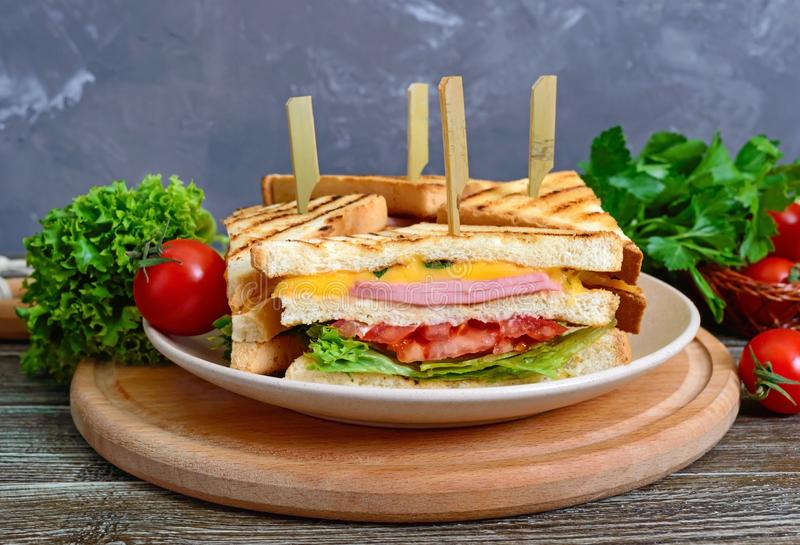 Club-sandwiches with crispy toast, sausage, cheese, tomato, greens. Traditional American snack stock photos
