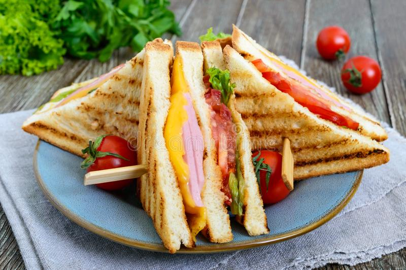 Club-sandwiches with crispy toast, sausage, cheese, tomato, greens. Traditional American snack stock images