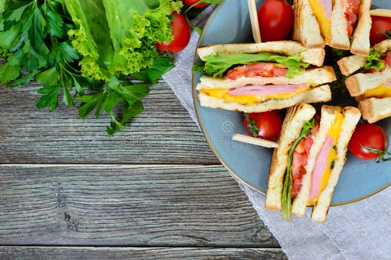 Club-sandwiches with crispy toast, sausage, cheese, tomato, greens. Traditional American snack. The top view royalty free stock images