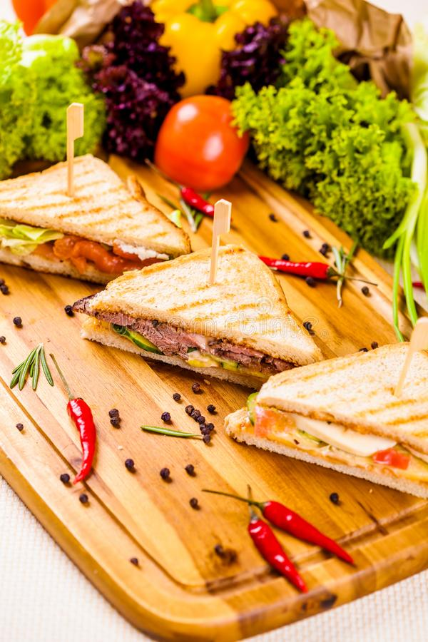 Club sandwiches with different fillings on wooden board royalty free stock photos