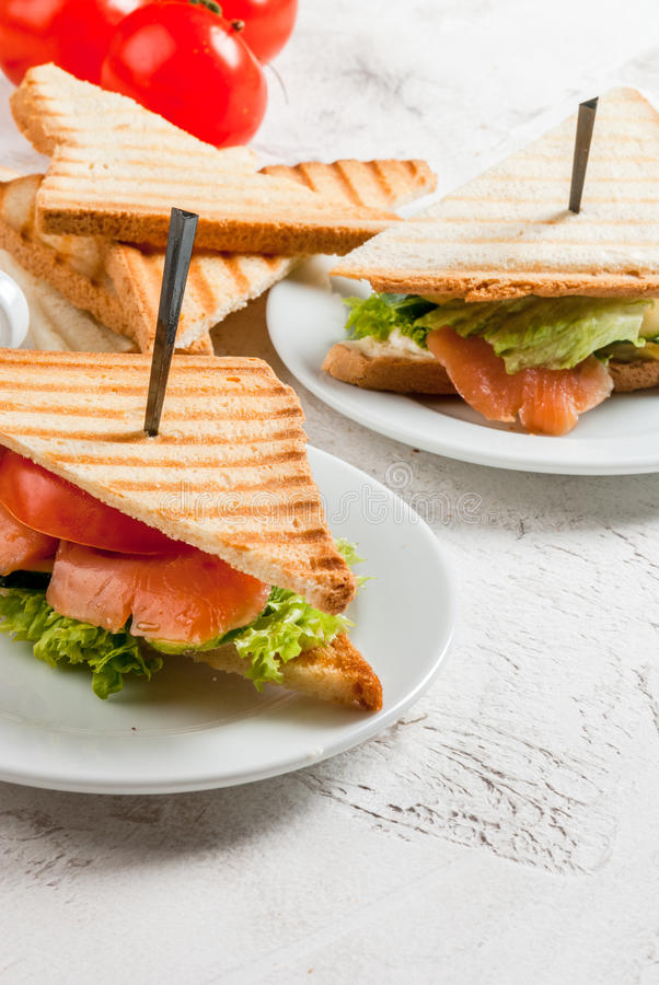 Club sandwiches with salmon. Breakfast with club sandwiches with fresh tomatoes, lettuce and cucumbers salmon trout, coffee and freshly squeezed juice, on white stock photography