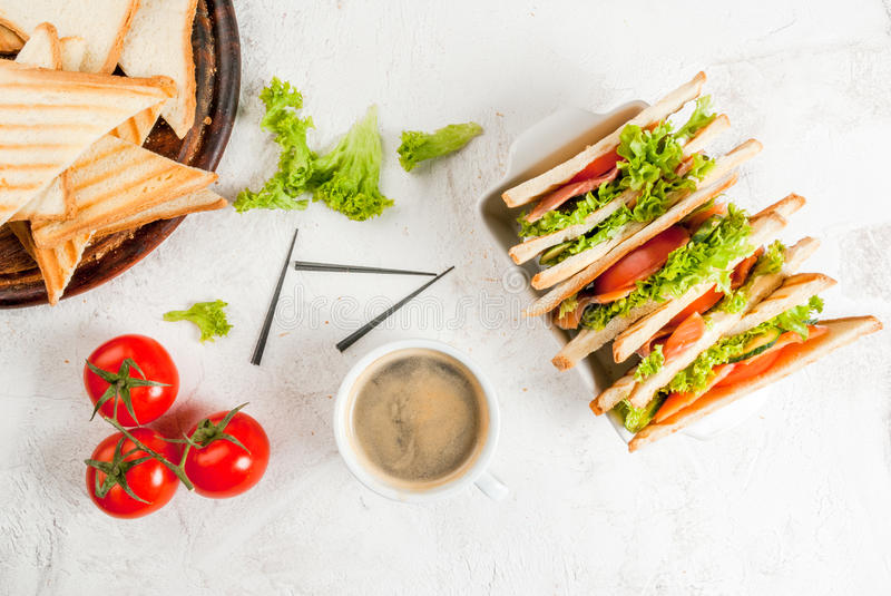 Club sandwiches with salmon. Breakfast with club sandwiches with fresh tomatoes, lettuce and cucumbers salmon trout, coffee, on white stone concrete table close stock image