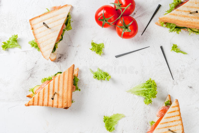 Club sandwiches with salmon. Club sandwiches with fresh lettuce, tomato, cucumber and salmon trout. On crunchy toast. With ingredients on white concrete stone royalty free stock photos