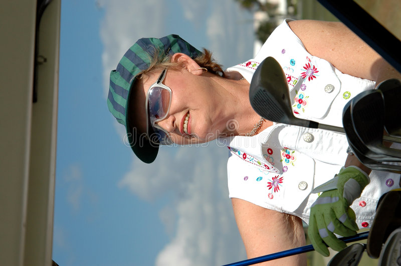 Club selection. Happy senior woman choosing her club from her bag in golf cart (close-up stock images