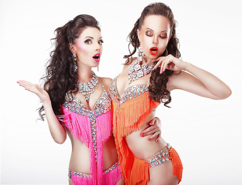 Clubbing. Two Women Showgirls in Stage Dresses. Couple of Fashionable Women Showgirls in Stagy Dresses posing stock images