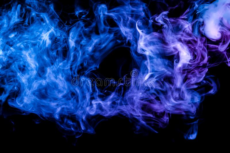Clubs of colored smoke of blue and pink color on a black isolated background in the form of clouds from the vape. Clubs of colored smoke of blue and pink color royalty free stock photography