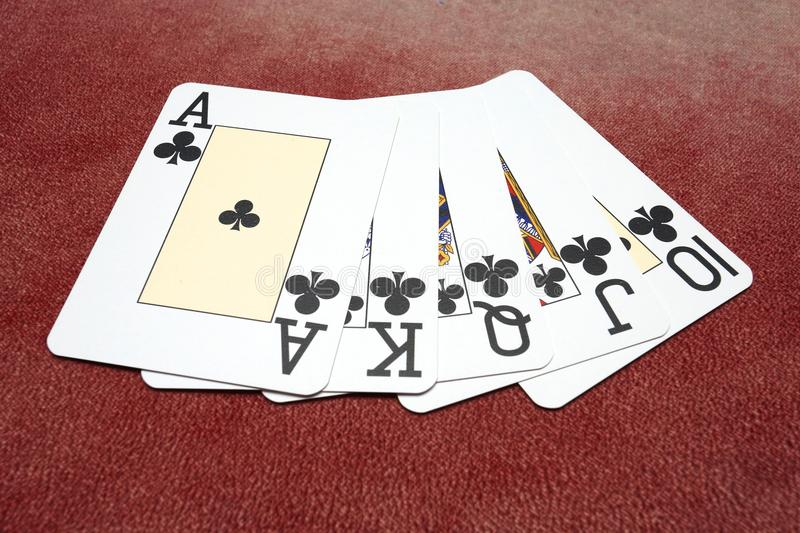 Clubs royal flush over red background stock images