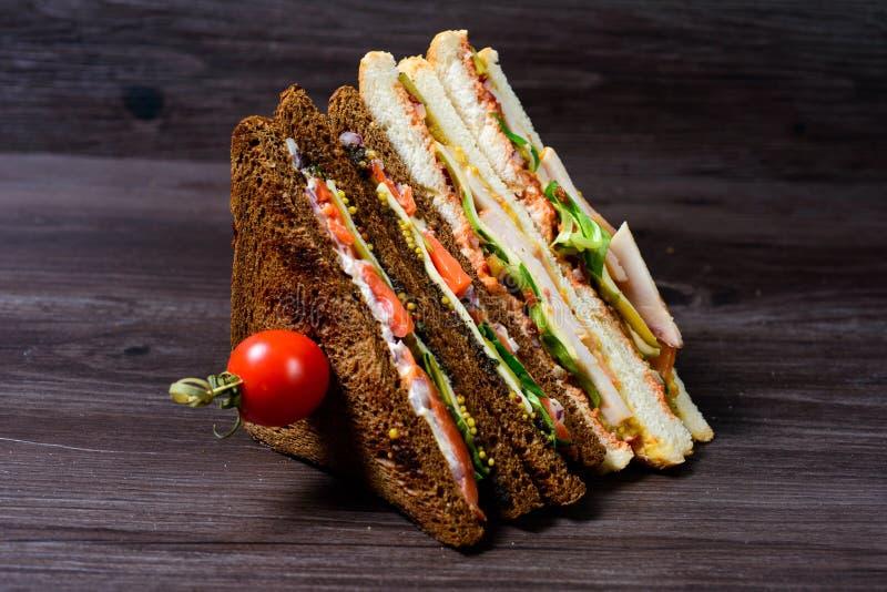 Clubsandwiches που προετοιμάζεται πρόσφατα σε έναν ξύλινο τέμνοντα πίνακα στοκ εικόνα