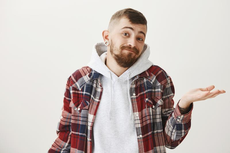 Clueless attractive guy having doubts. Portrait of handsome european male student with beard and ear tunnels shrugging. Raising palm and listing eyebrows with royalty free stock photography
