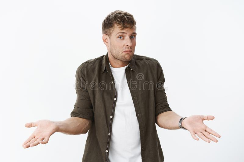 Clueless guy shrugging shoulders as being unaware. Portrait of confused cute blond man holding hands sideways dazed. Pursing lips and lifting eyebrows stock photography