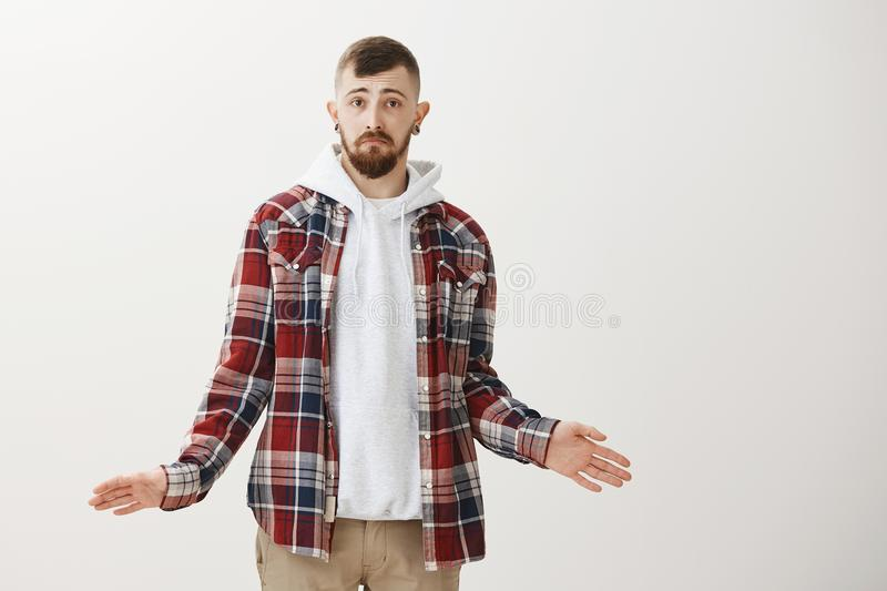 Clueless handsome male student with beard and stylish haircut spreading palms and shrugging with sturgeon face, being. Confused and questioned, having no idea stock photography