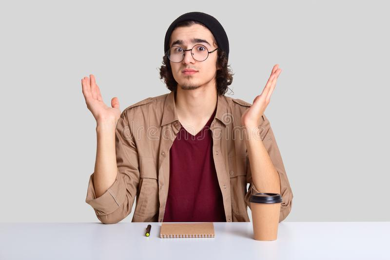 Clueless hesitant youngster spread palms with apathy, looks with puzzlement, wears round optical glasses, hat and shirt, has no. Ideas what to write, drinks royalty free stock photo