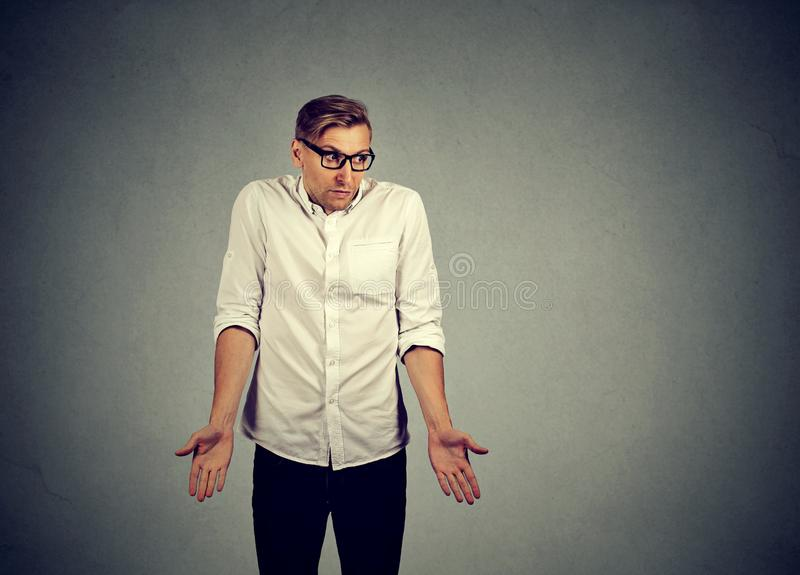 Clueless young man shrugging shoulders stock images