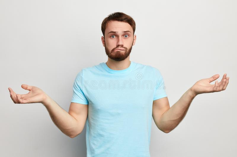 Clueless puzzled funny man biting his lips. Clueless puzzled funny man with widely opened eyes having hesitation shrugging his shoulders , biting his lips royalty free stock photography