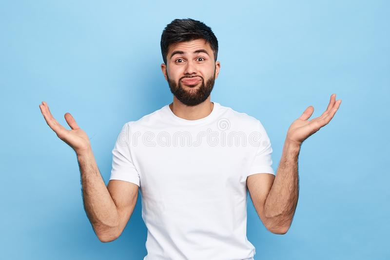 Clueless puzzled handsome guy having hesitation, shrugging his shoulders. Facial expressions. young bearded man cannot solve his problems, close up portrait stock image