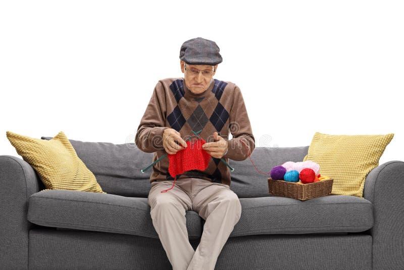 Clueless senior sitting on a sofa and knitting. Isolated on white background stock photo