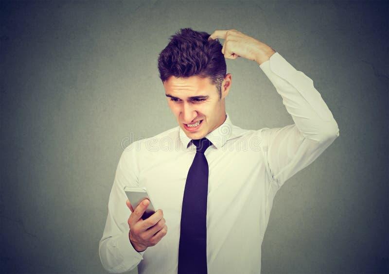 Clueless verwarde bedrijfsmens die problemen met zijn smartphone hebben stock foto's