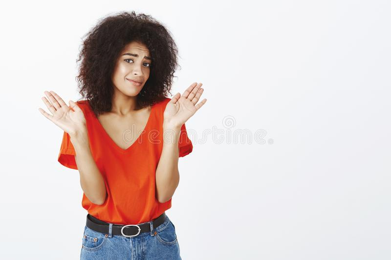 Clueless woman prefers stay away from troubles. Indifferent unaware attractive girlfriend with dark skin and afro royalty free stock images