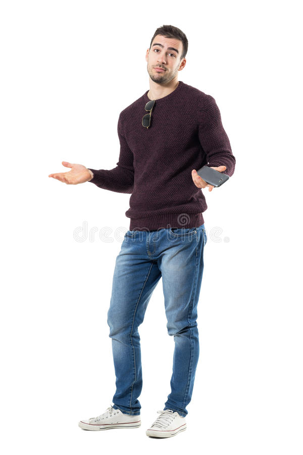 Clueless young casual man shrugging shoulders holding mobile phone. Full body length portrait isolated over white studio background royalty free stock images