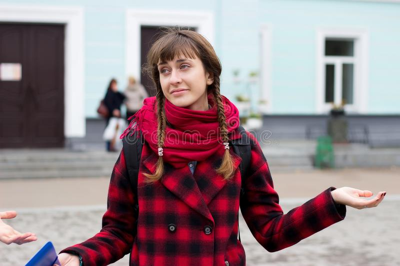 Clueless young woman, student, worker arms out asking what`s the problem who cares so what, I dont know. royalty free stock image