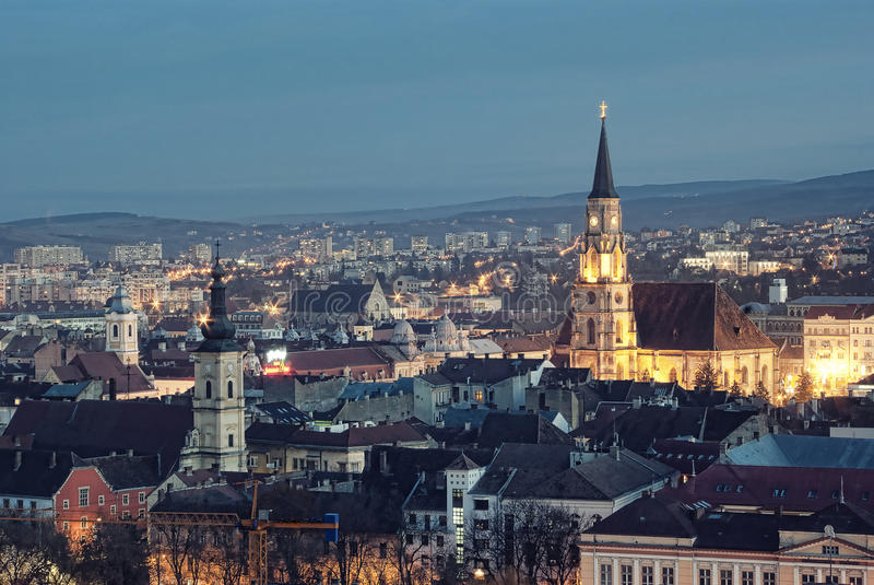 Cluj Napoca at dusk. Overview of the city of Cluj Napoca at dusk, with Saint Michael's church illuminated. Romanian travel image stock image