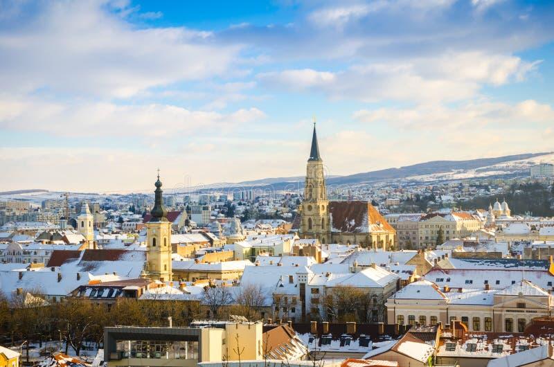 Cluj Napoca mening op een zonnige blauwe dag van de wolkenwinter met St Michael Church stock foto's