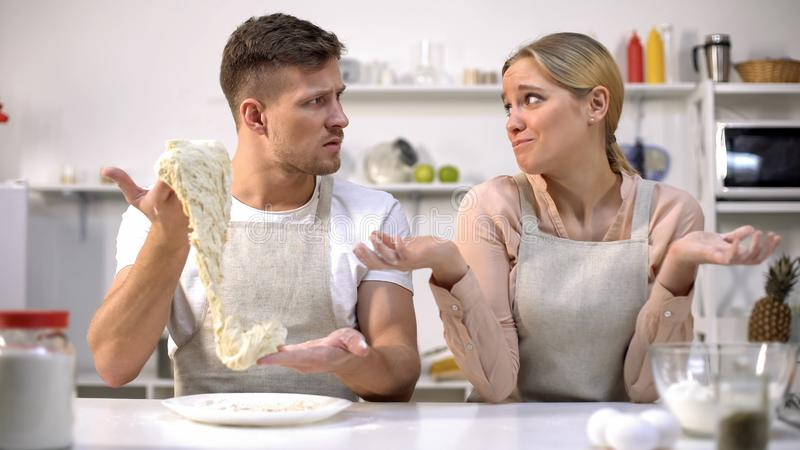 Clumsy man stretching dough, looking at wife, difficulties during cooking. Clumsy men stretching dough, looking at wife, difficulties during cooking, stock photo stock photos